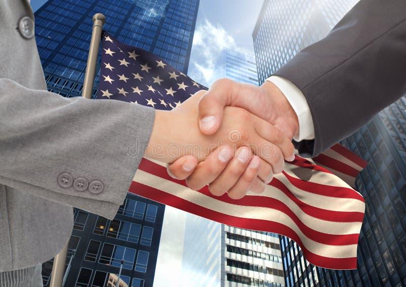 Hombres de negocios que sacuden sus manos contra bandera americana y rascacielos foto de archivo