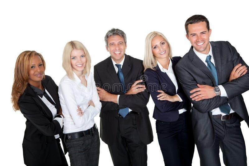 Hombres de negocios que se colocan con las manos plegables foto de archivo