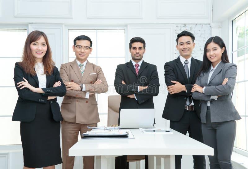 hombres de negocios que se colocan con los brazos cruzados en oficina imagen de archivo