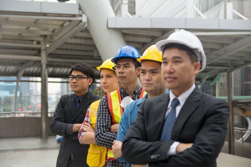 Hombres de negocios que se colocan en fila para presentar éxito empresarial foto de archivo