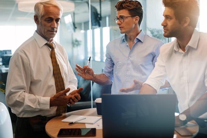 Hombres de negocios que se colocan en la tabla y la discusión imagenes de archivo