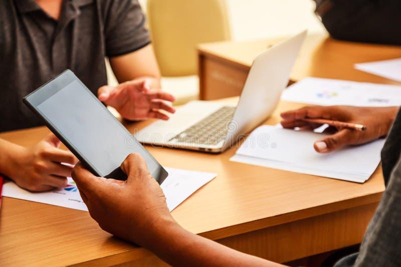 Hombres de negocios que se encuentran en el concepto de la oficina, usando ideas, cartas, ordenadores, tableta, dispositivos eleg imagen de archivo libre de regalías