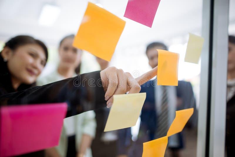 Hombres de negocios que se encuentran en la oficina y que explican a los colegas sobre notas pegajosas en taller de la estrategia foto de archivo libre de regalías