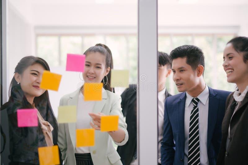 Hombres de negocios que se encuentran en la oficina y que explican a los colegas sobre notas pegajosas en taller de la estrategia fotos de archivo libres de regalías