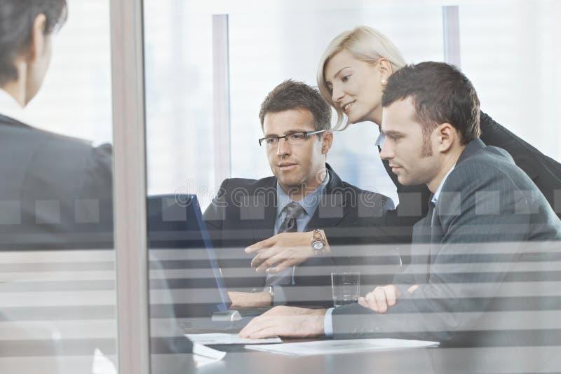 Hombres de negocios que se encuentran en la sala de reunión detrás del vidrio imagenes de archivo