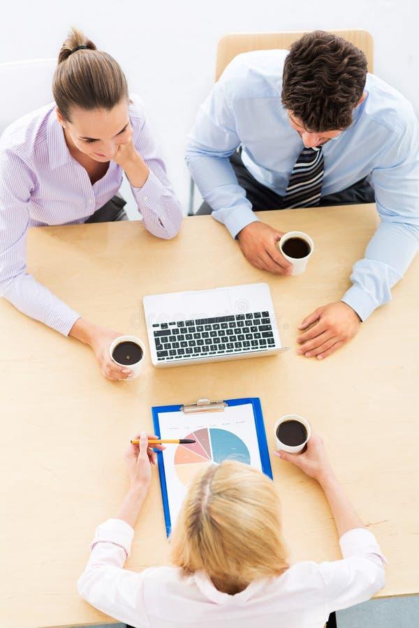 Hombres de negocios que se encuentran en la tabla fotografía de archivo
