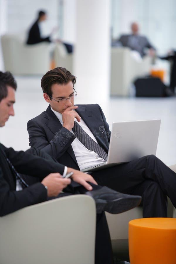 Hombres de negocios que se encuentran en un pasillo imagen de archivo