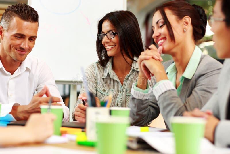 Hombres de negocios que se sientan alrededor de la tabla en la reunión fotos de archivo libres de regalías