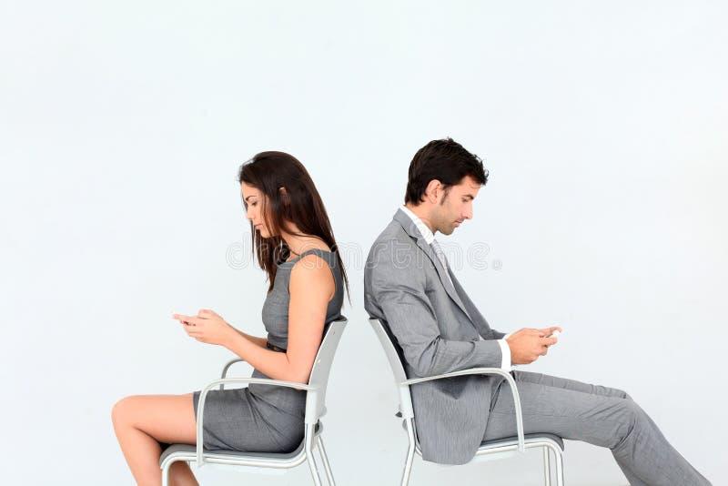 Hombres de negocios que se sientan de nuevo a la parte posterior usando smartphones foto de archivo