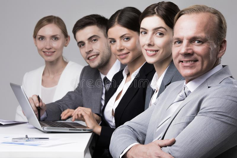 Hombres de negocios que se sientan en fila foto de archivo