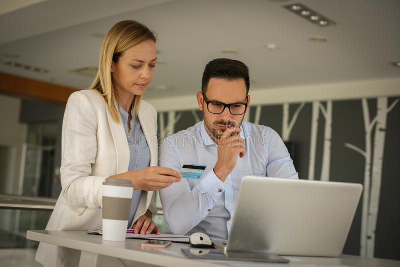 Hombres de negocios que se sientan en oficina y que usan la tarjeta de crédito megabus imágenes de archivo libres de regalías