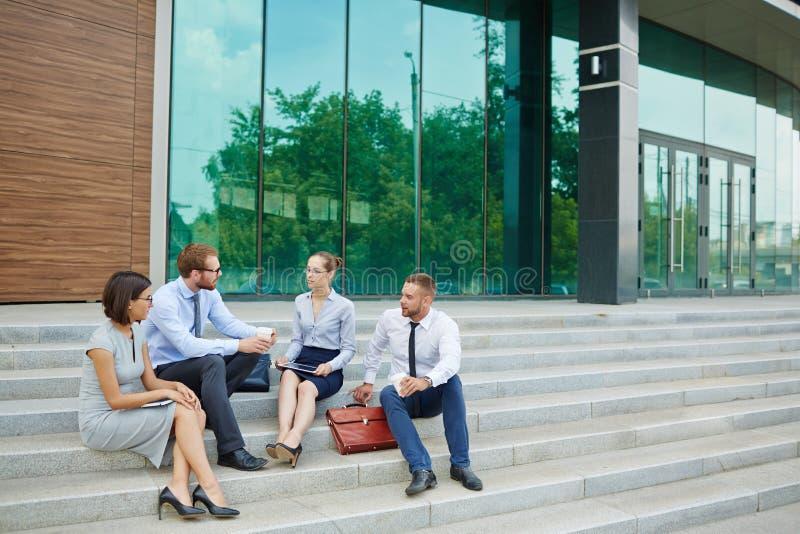 Hombres de negocios que se sientan en pasos del edificio de oficinas fotos de archivo