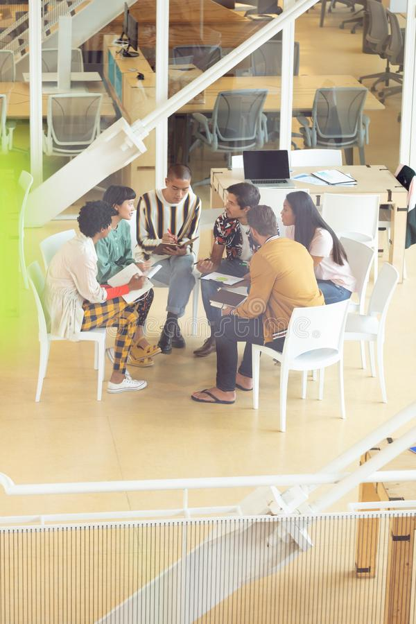 Hombres de negocios que se sientan junto y que tienen discusión de grupo en oficina imágenes de archivo libres de regalías