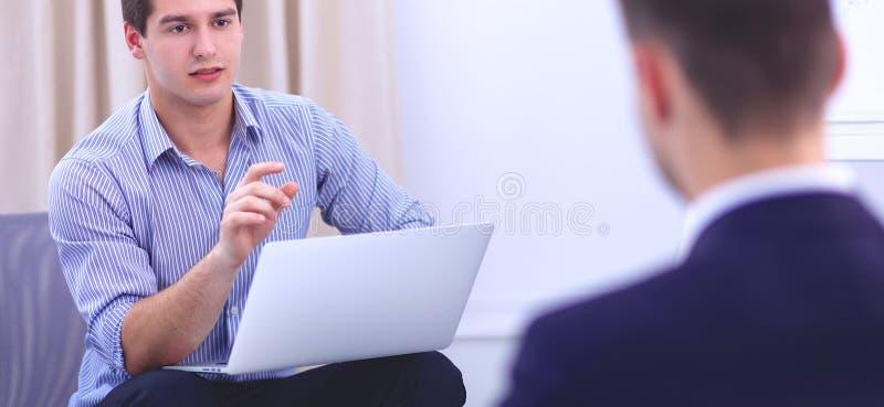 Hombres de negocios que se sientan y que discuten en la reunión de negocios, en oficina fotos de archivo