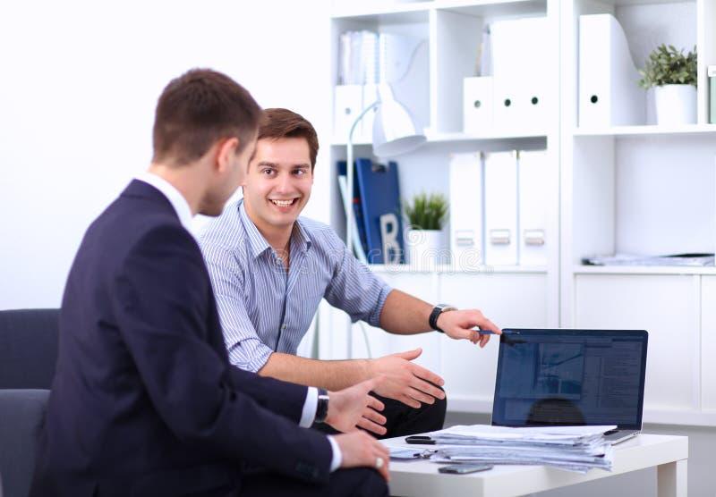 Hombres de negocios que se sientan y que discuten en la reunión, en oficina imagenes de archivo