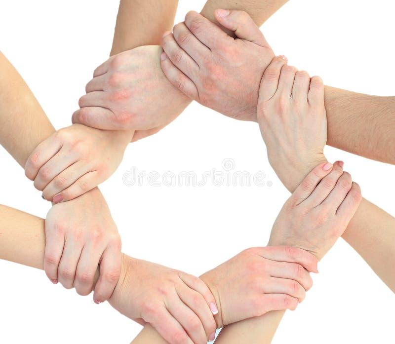 Hombres de negocios que se unen a las manos en un círculo en la oficina fotos de archivo