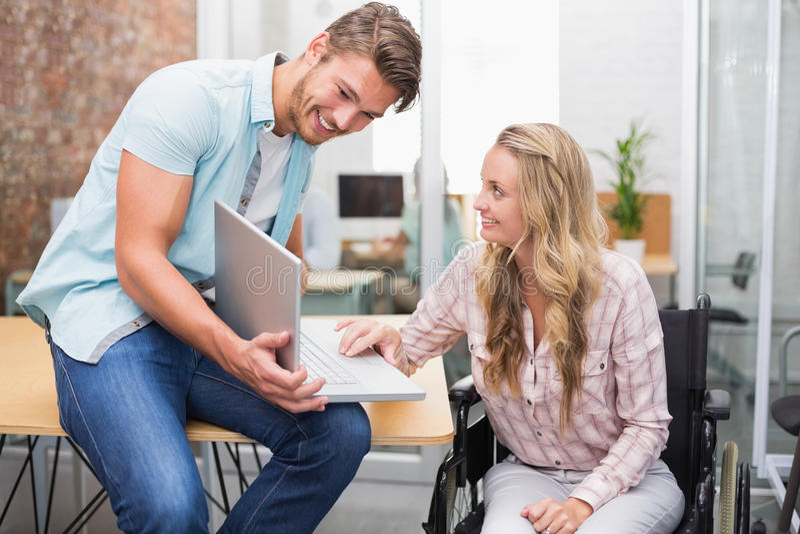 Hombres de negocios que sonríen y que trabajan así como un ordenador portátil foto de archivo libre de regalías