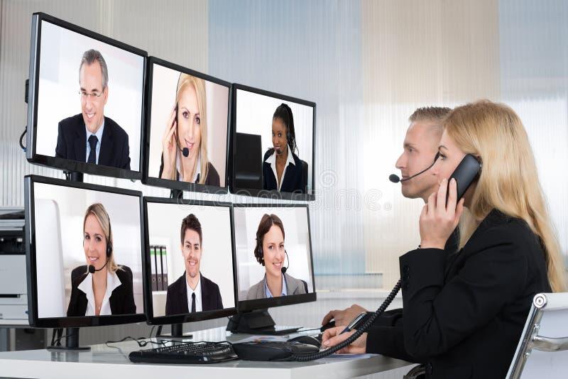 Hombres de negocios que tienen audioconferencia imagen de archivo libre de regalías