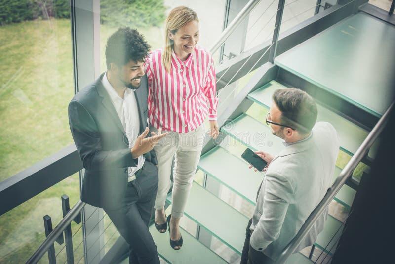 Hombres de negocios que tienen conversación en oficina del edificio imagenes de archivo