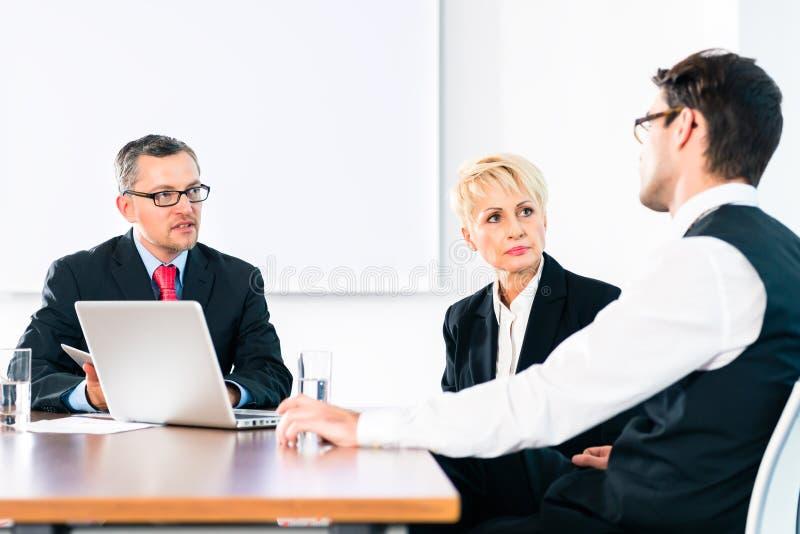 Hombres de negocios que tienen conversaciones en oficina foto de archivo libre de regalías