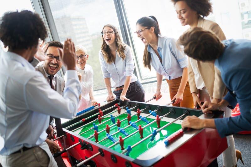 Hombres de negocios que tienen gran tiempo junto Colegas que juegan a fútbol de la tabla en oficina moderna fotografía de archivo