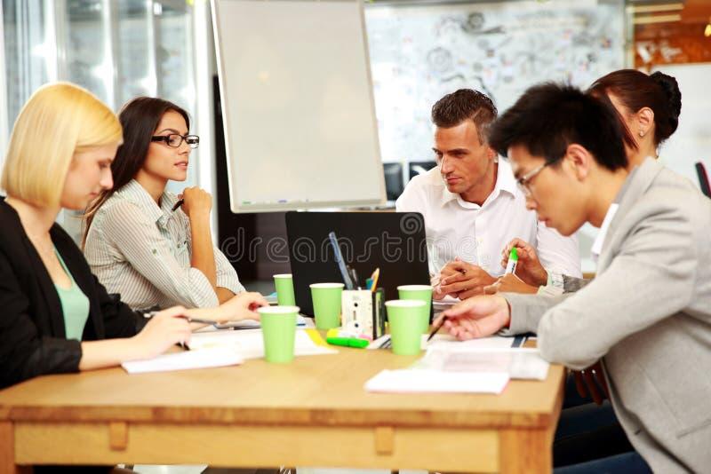 Hombres de negocios que tienen reunión alrededor de la tabla imagen de archivo