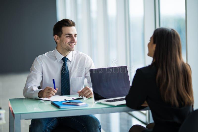 Hombres de negocios que tienen reunión alrededor del vector en oficina moderna El hombre joven escucha mujer en oficina imagen de archivo