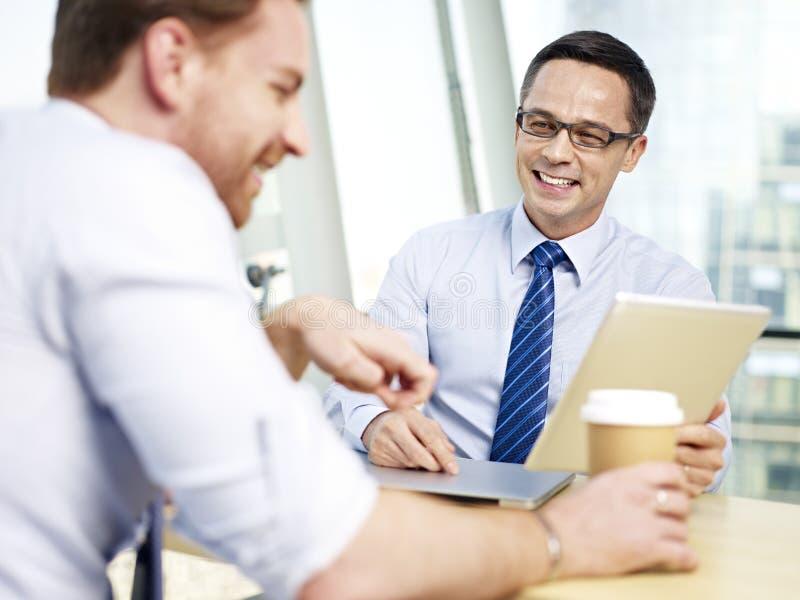 Hombres de negocios que tienen una conversación agradable imagen de archivo libre de regalías