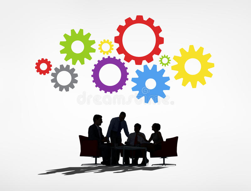Hombres de negocios que tienen una reunión y engranajes arriba foto de archivo