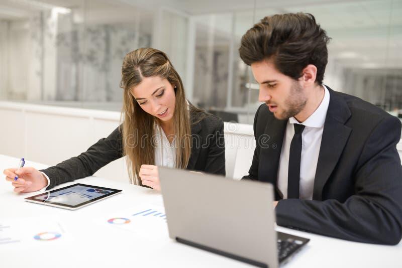 Hombres de negocios que trabajan alrededor de la tabla en oficina moderna foto de archivo
