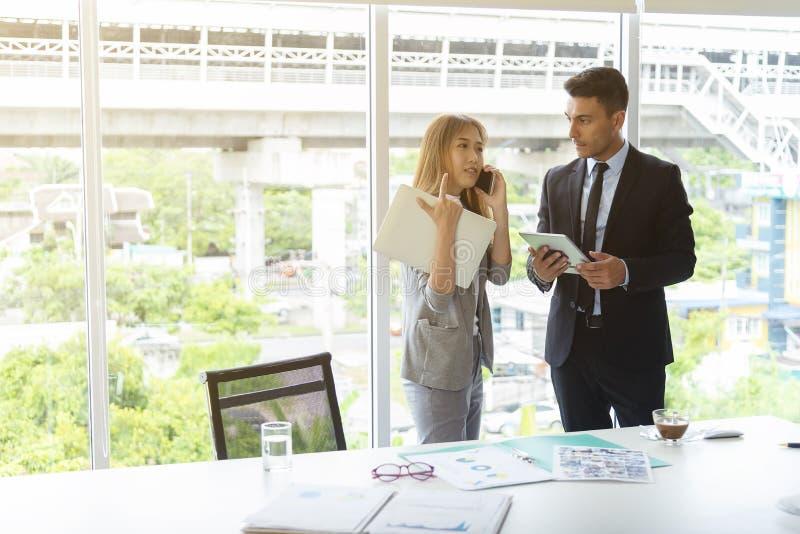 Hombres de negocios que trabajan en oficina Usando móvil y la tableta para la conferencia en línea con el socio fotografía de archivo