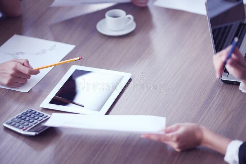 Hombres de negocios que trabajan junto en la reuni?n imagen de archivo libre de regalías