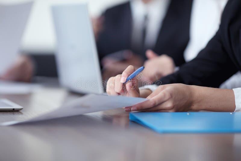 Hombres de negocios que trabajan junto en la reuni?n fotografía de archivo