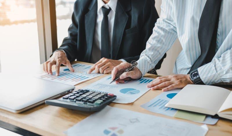 Hombres de negocios que trabajan junto en la tabla del sitio de la oficina y el presupuesto de equilibrio fotografía de archivo libre de regalías