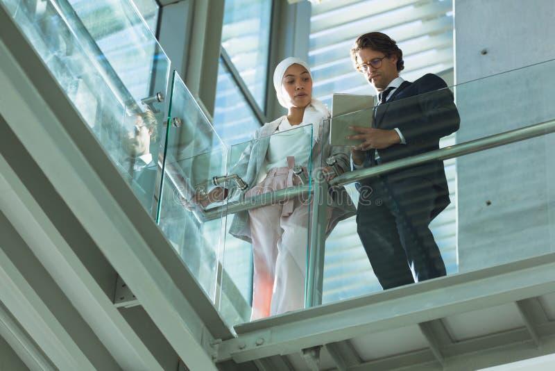 Hombres de negocios que trabajan junto en la tableta digital cerca de la verja en pasillo en la oficina moderna fotos de archivo