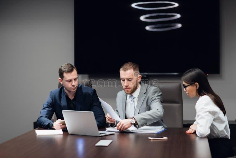 Hombres de negocios que trabajan junto en su ordenador portátil en una sala de reunión imagen de archivo