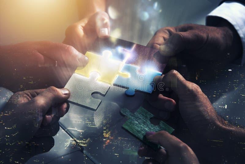 Hombres de negocios que trabajan junto para construir un rompecabezas Concepto de trabajo en equipo, de sociedad, de integración  imagen de archivo