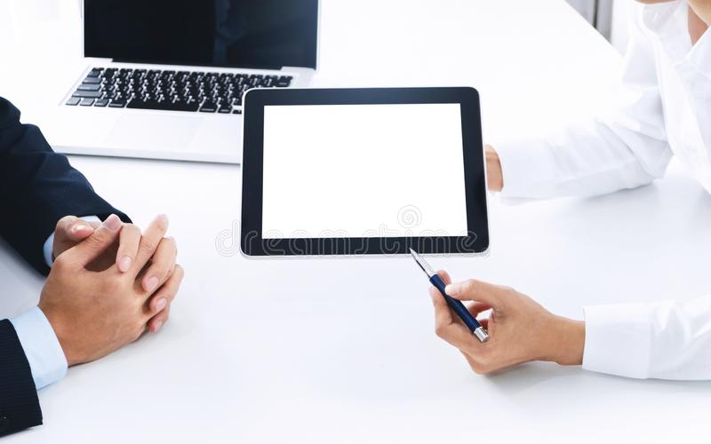 Hombres de negocios que trabajan junto y que usan la tableta digital de la pantalla en blanco en un lugar de trabajo fotografía de archivo