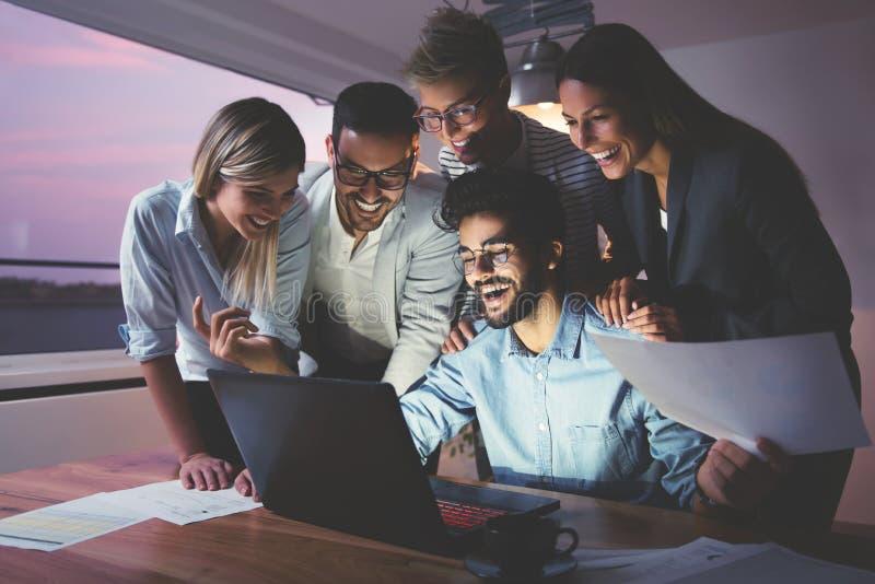 Hombres de negocios que trabajan tarde junto en equipo imágenes de archivo libres de regalías