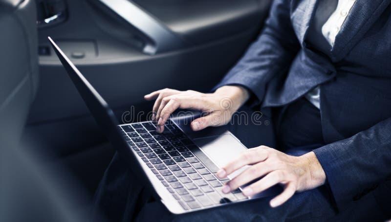 Hombres de negocios que usan el coche del establecimiento de una red del ordenador portátil dentro foto de archivo
