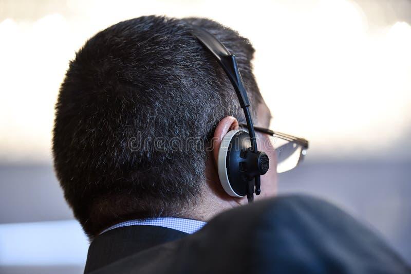 Hombres de negocios que usan los auriculares para la traducción imagen de archivo libre de regalías