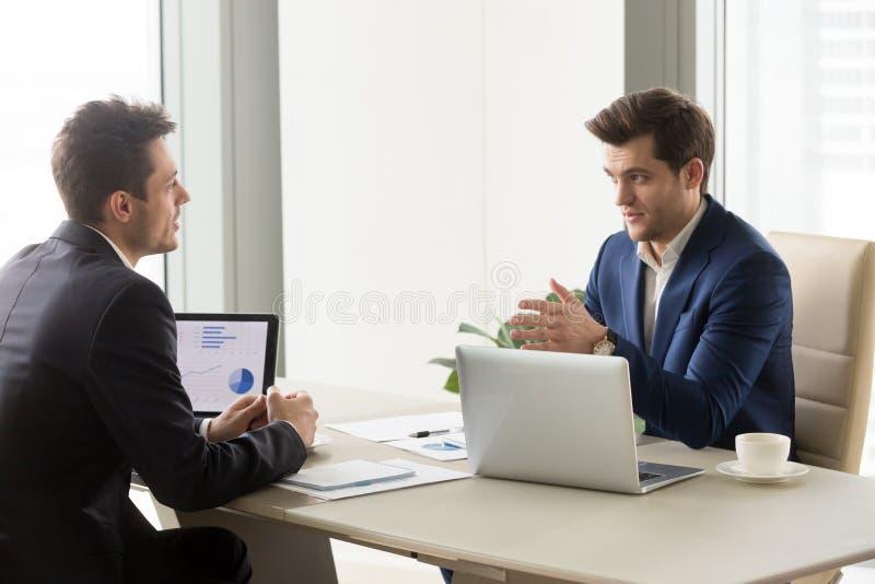 Hombres de negocios serios en oficina que discuten el proyecto, analizando el carbón de leña imagen de archivo libre de regalías