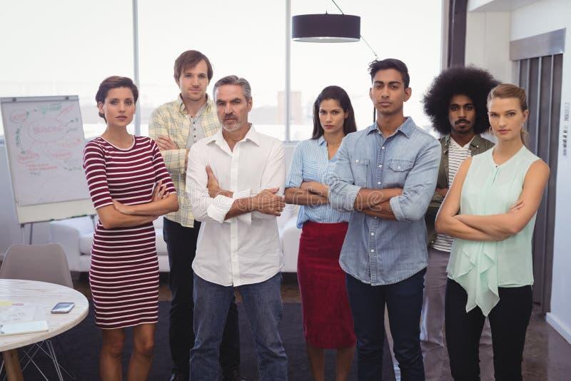 Hombres de negocios serios que se colocan en oficina creativa imágenes de archivo libres de regalías