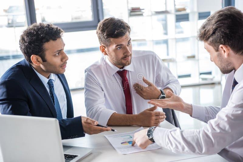 Hombres de negocios serios que se sientan en la tabla y que discuten diagramas en oficina fotos de archivo