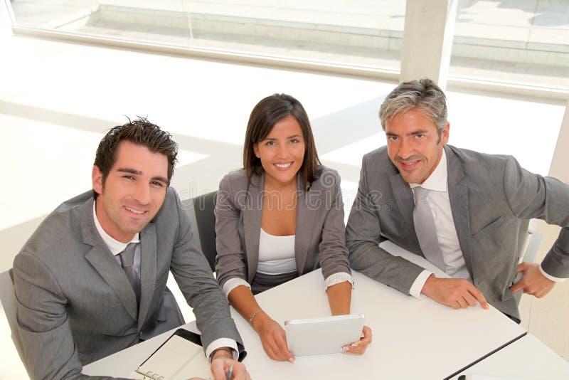 Hombres de negocios sonrientes alrededor de la tablilla de la reunión imagenes de archivo