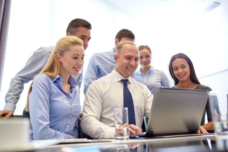 Hombres de negocios sonrientes con el ordenador portátil en oficina imagen de archivo