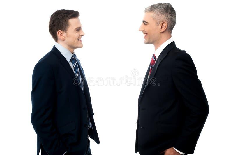 Hombres de negocios sonrientes en la discusión foto de archivo libre de regalías