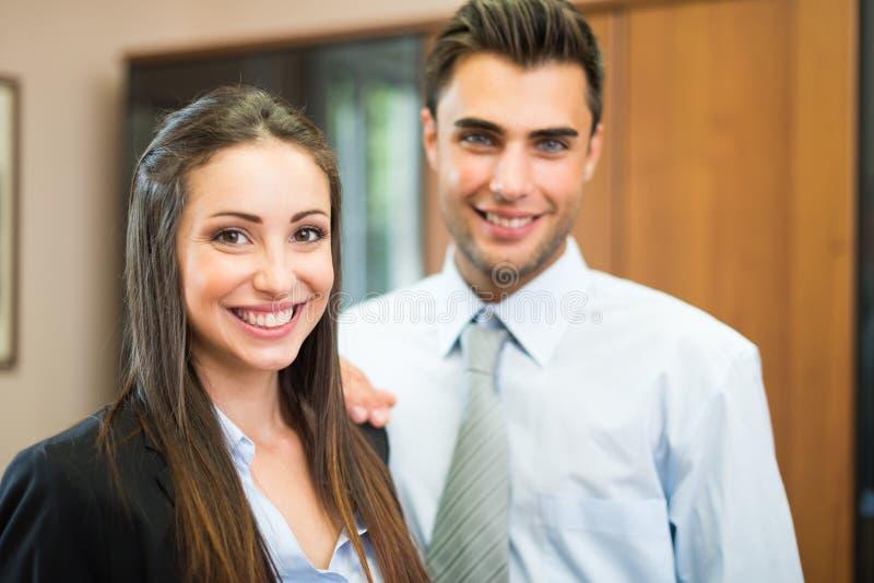 Hombres de negocios sonrientes en su oficina imagen de archivo