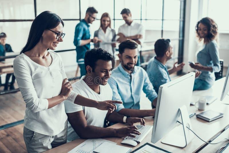 Hombres de negocios sonrientes jovenes que trabajan en oficina fotografía de archivo libre de regalías