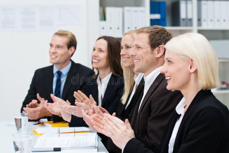 Hombres de negocios sonrientes que aplauden sus manos imagenes de archivo